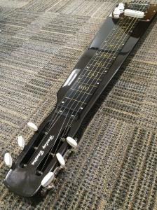 Photo of lap-steel guitar on carpet